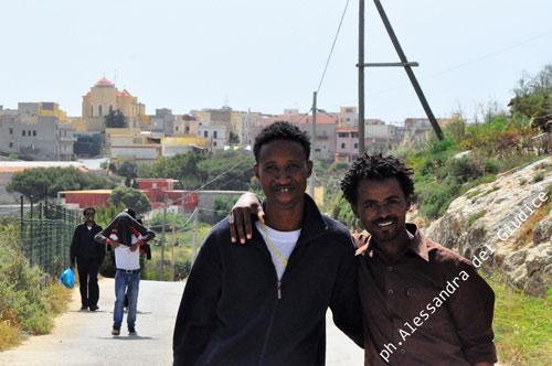 due ragazzi abbracciati camminano per la strada di Lampedusa